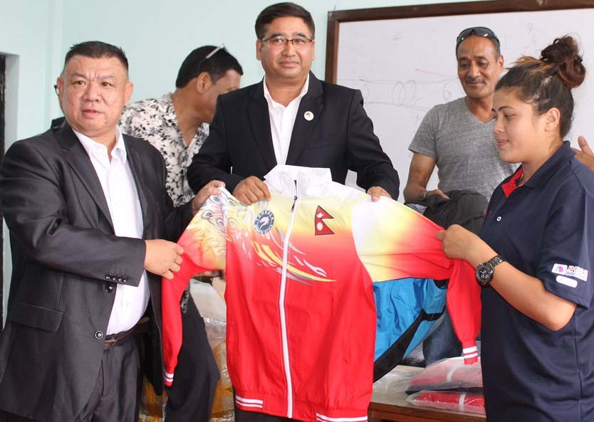 Nepal Olympic Committee president Jeevan Ram Shrestha(Centre) hands over the sports kit to the players going to participate in Rio Olymics 2016, in Kathmandu, on Sunday, July 24, 2016. Photo: THT