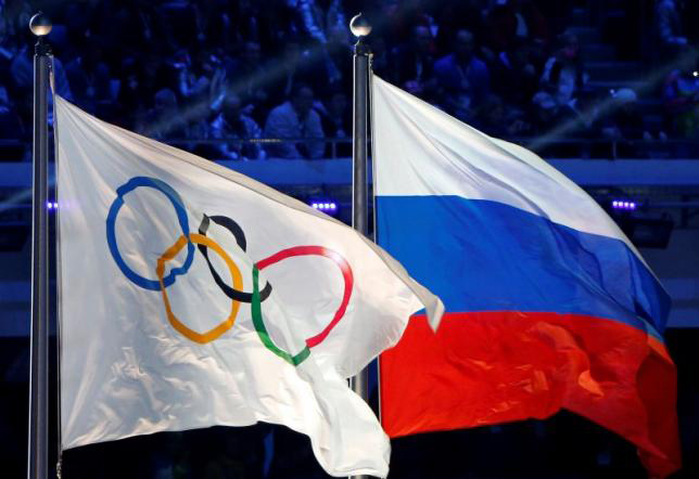 The Russian national flag (R) and the Olympic flag are seen during the closing ceremony for the 2014 Sochi Winter Olympics, Russia on February 23, 2014.nPhoto: Reuters/File Photo
