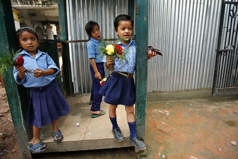 Schoolgirls hold flowers for their teachers during Guru Purnima or Teacher's day, a festival dedicated to teachers, in Durbar High School,  Kathmandu, on Tuesday, July 19, 2016. Photo: Skanda Gautam/ THT