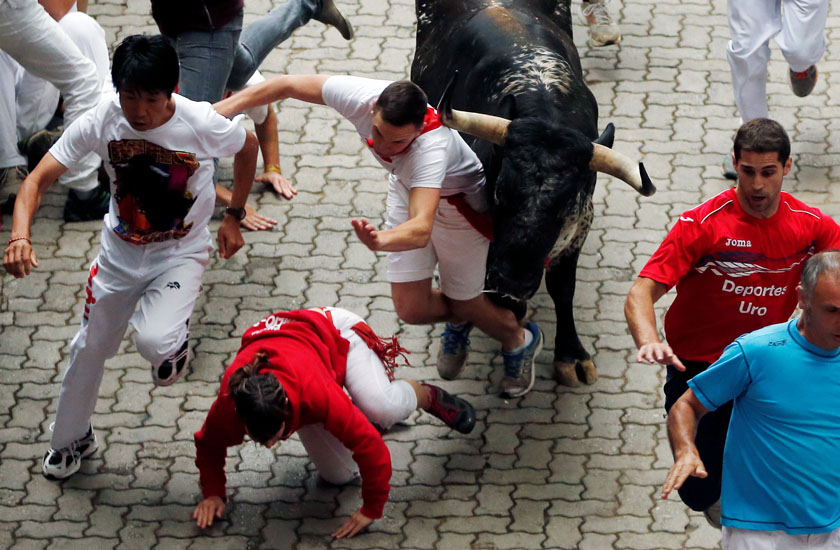 Runners fall in front of a Victoriano del Rio bull during the sixth running of the bulls at the San Fermin festival in Pamplona, northern Spain, July 12, 2016. Photo: Reuters