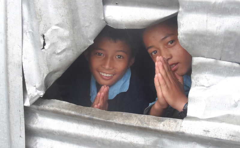 Two students greet as a photograph of their temporary learning centre is captured at the Kerauja Secondary School, in Kerauja in Gorkha district, on Sunday, July 3, 2016. The school is operating from the temporary learning centre as a landslide threatened safety of its permanent structure. Photo: RSS