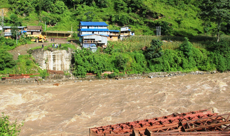 An under-construction bridge is swept away by the flooded Tamor River in Dobhan of Taplejung district, on Saturday, July 16, 2016. Photo: RSS