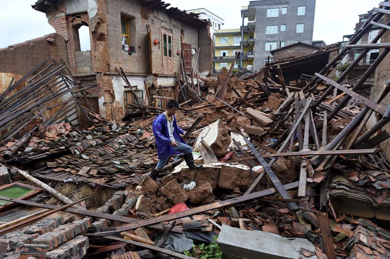 In this July 9, 2016 photo, a villager walks around a destroyed house, after torrential rainfall brought by typhoon Nepartak, in Lingcuo village of Xindu Township in Putian, southeast China's Fujian Province. Photo: AP