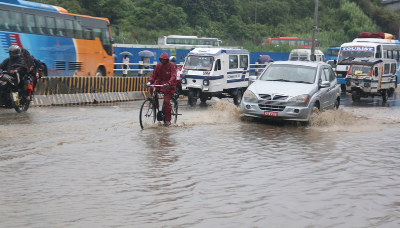 Vehicles struggle to pass along a waterlogged road after a brief rainfall, in Koteshwor of Kathmandu, on Saturday, July 3, 2016. Photo: RSS