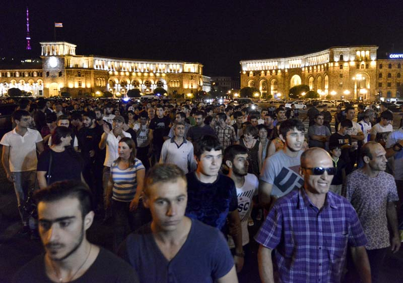 Protesters march during a night rally to support the radical opposition group gunmen in the Republican Square in Yerevan, Armenia on Sunday, July 31, 2016. Photo: AP