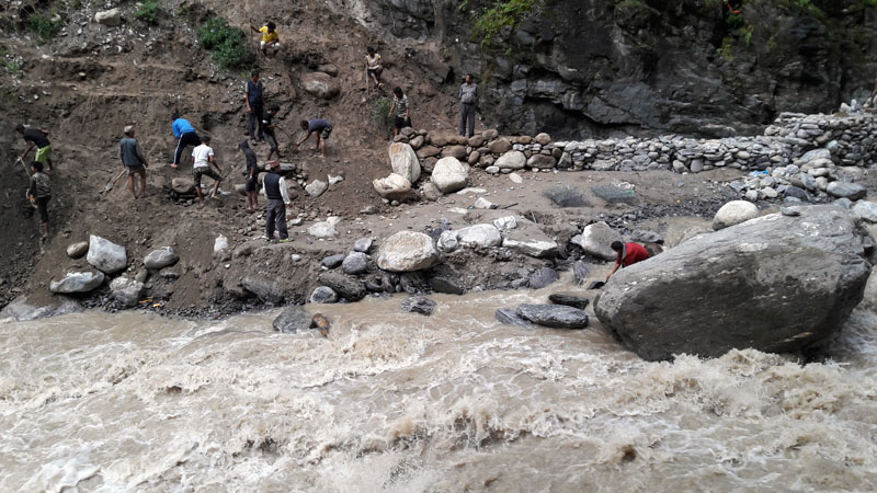 Locals constructing a canal after a flood in Bahuli Khola swept away the canal of Triveni Small Hydro Project in Martadi, Bajura, on Thursday. THT