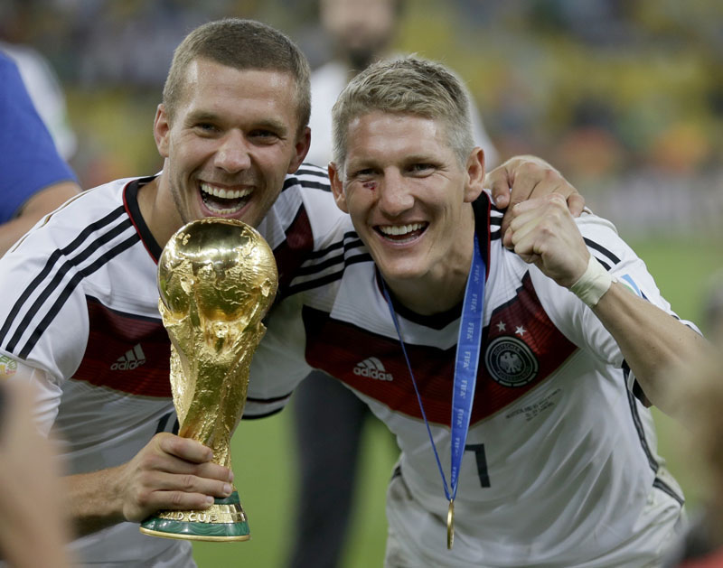 FILE - Germany's Bastian Schweinsteiger and Lukas Podolski (left) celebrate with the World Cup trophy following their 1-0 victory over Argentina after the World Cup final football match between Germany and Argentina at the Maracana Stadium in Rio de Janeiro, Brazil, on July 13, 2014. Photo: AP