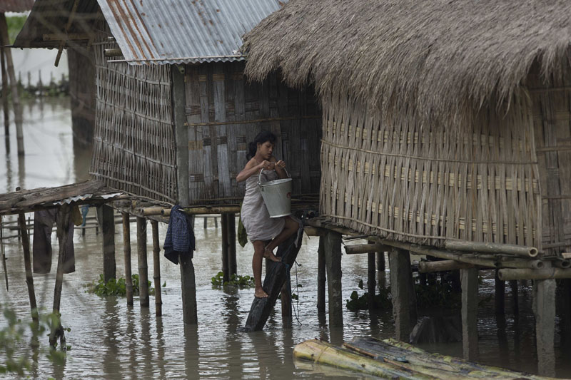 An Indian Mishing tribal woman climbs to her traditional hut surrounded by flood waters carrying drinking water after arriving in a banana raft, bottom right at Majuli, a river island east of Guwahati, northeastern Assam state, India, on Wednesday, July 27, 2016. Photo: AP