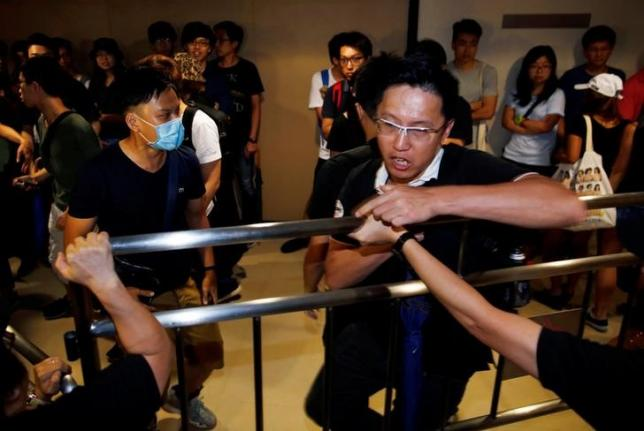 Supporters of Hong Kong Indigenous member Edward Leung try to break into the venue during a briefing for qualified candidates running for the Legislative Council election in Hong Kong, China, August 2, 2016. REUTERS/Tyrone Siu