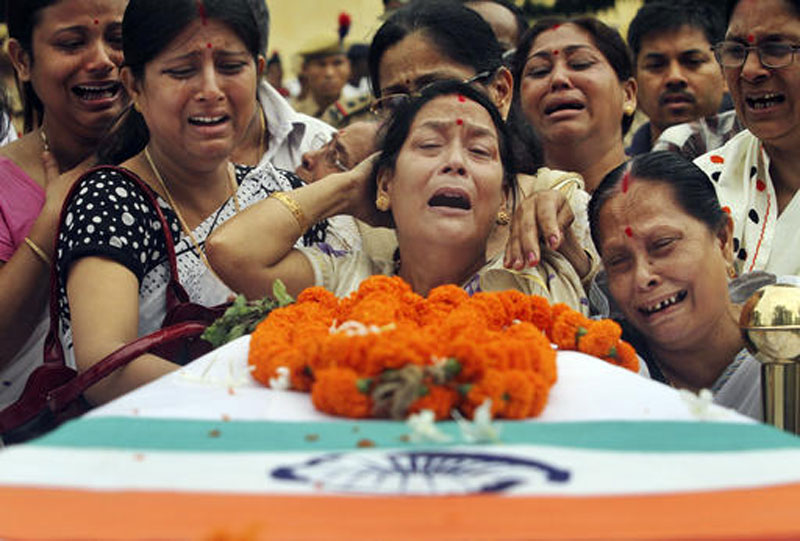 FILE u2013 In this June 7, 2014 file photo, relatives mourn by the coffin containing the body of a police officer Nityananda Goswami, who was killed in a rebel attack, as they load his body in a vehicle during his guard of honor function in Gauhati, in the northeastern Indian state of Assam. AP