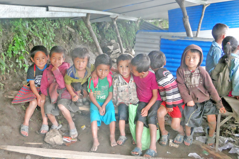 Small students are compelled to attend their classes in a makeshift school in Manpu-9 of Gorkha district, on Tuesday, August 23, 2016. Delay in reconstruction of the school damaged in last year's devastating earthquake has hampered their studies. Photo: RSS