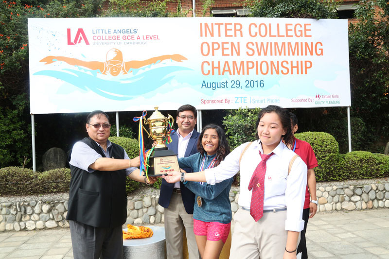 Jeevan Ram Shrestha, President of Nepal Olympic Committee and Founder Chairman of Little Angelsu2019 Umesh Shrestha handing over the trophy to LA team members after the Inter-college Swimming Championship on Tuesday. Photo: THT