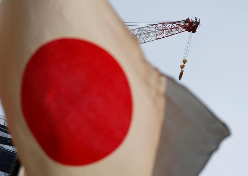 A crane at a construction site is seen behind Japan's national flag in Tokyo, Japan, on August 12, 2016. Photo: Reuters