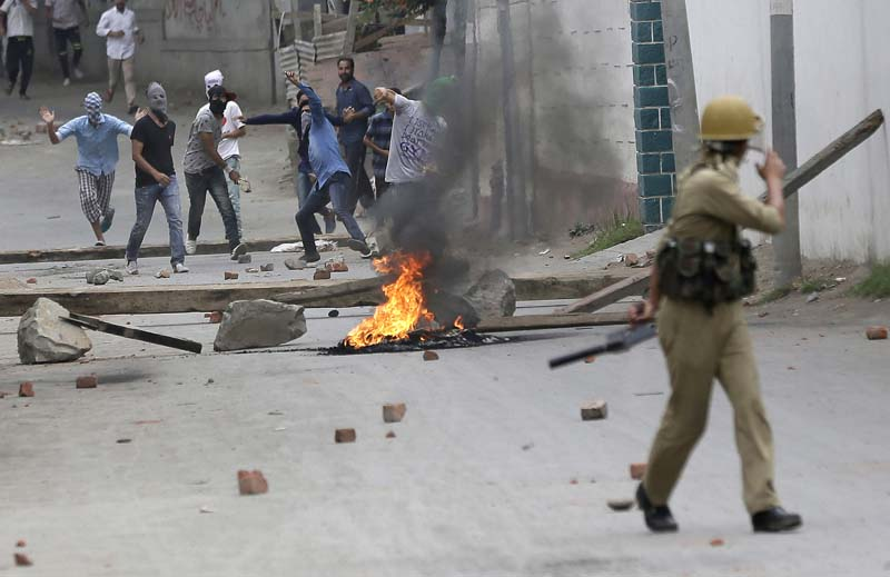 File- Masked Kashmiri protesters throw stones at police in Srinagar, Indian-controlled Kashmir, on August 10, 2016. Photo: AP