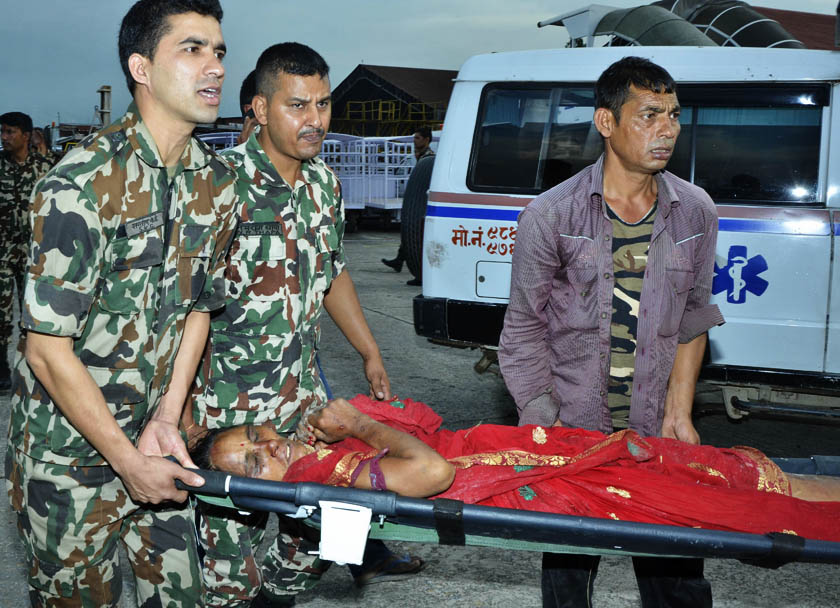 Nepal Army personnel transferring an injured person to an ambulance from a helicopter.