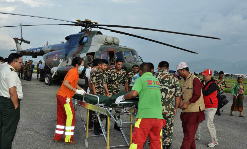 Nepal Army personnel transferring an injured person to an ambulance from a helicopter. Photo: Nepal Army