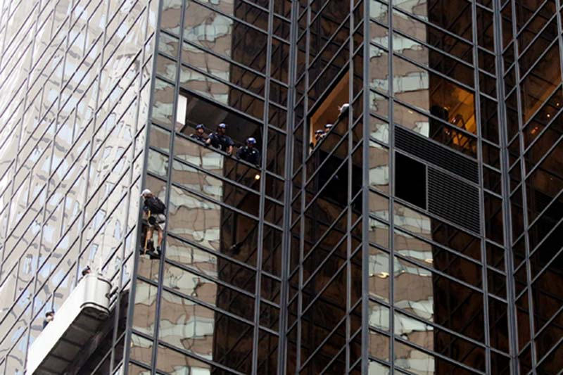 Officers from the NYPD attempt to detain a man as he climbs the outside of Trump Tower in New York, US, on August 10, 2016. Photo: Reuters