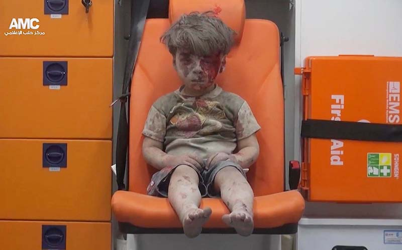 In this frame grab taken from video provided by the Syrian anti-government activist group Aleppo Media Centre (AMC), a child sits in an ambulance after being pulled out of a building hit by an airstrike, in Aleppo, Syria, on Wednesday, August 17, 2016. Photo: AP