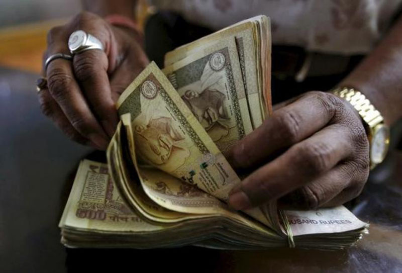 A money lender counts Indian rupee currency notes at his shop in Ahmedabad, India, May 6, 2015. Photo: Reuters