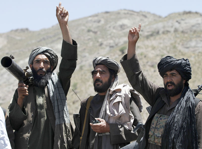 FILE - In this May 27, 2016  file photo, Taliban fighters react to a speech by a senior leader of a breakaway faction of the Taliban, Mullah Abdul Manan Niazi, in the Shindand district of Herat province, Afghanistan. Photo: AP