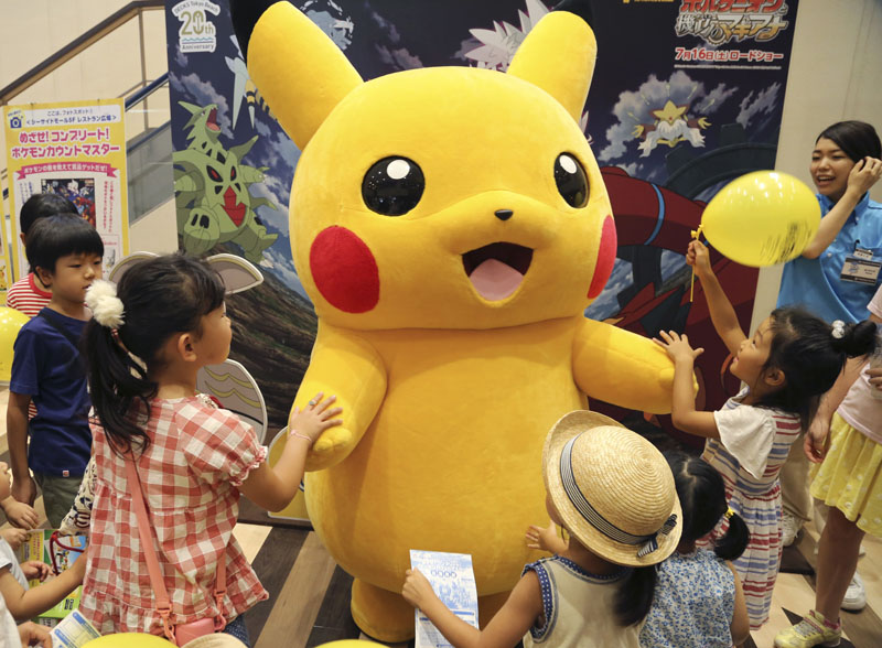 FILE - In this July 18, 2016, file photo, a stuffed toy of Pikachu, a Pokemon character, is surrounded by children during a Pokemon festival in Tokyo. A real-life Pikachu statue appeared in a New Orleans park. New Orleans police told ABC News for a story published August 2, 2016, that they have no plans to remove it. (AP Photo/Koji Sasahara, File)