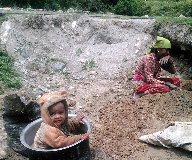 FILE: A child plays as his mother works at a nearby field in Dolpa, on Sunday, August 21, 2016. Rampant poverty has compelled locals of Dolpa to work as labourers to earn their living. Photo: RSS