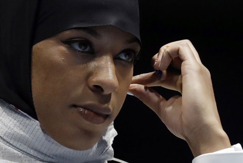 Ibtihaj Muhammad of the United States adjusts her hijab prior to competing with Olena Kravatska of Ukraine in the women's individual saber fencing event at the 2016 Summer Olympics in Rio de Janeiro, Brazil, on Monday, August 8, 2016. Photo: AP