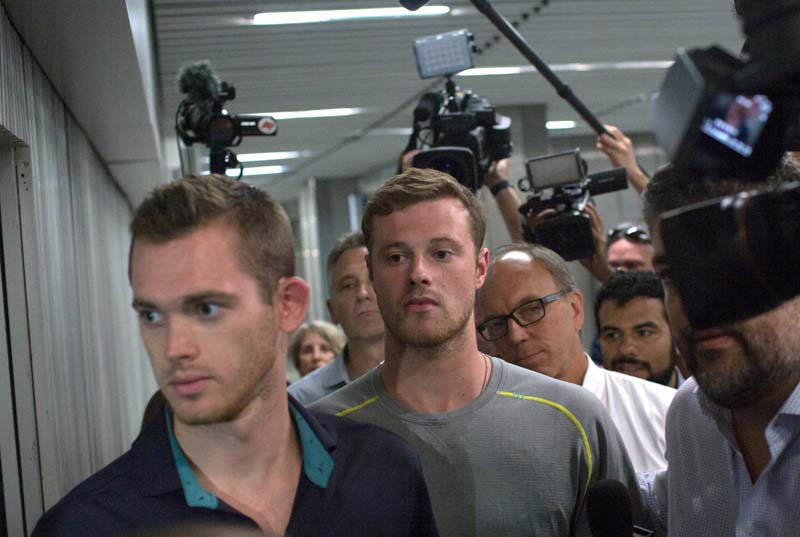 Journalists surround American Olympic swimmers Gunnar Bentz (left) and Jack Conger (centre) as they leave the police station at Rio International airport early Thursday Aug. 18, 2016. Photo: AP