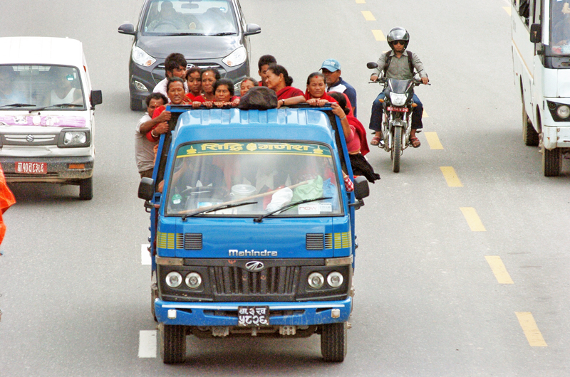 A pick-up truck carrying passengers along the Bhaktapur-Koteshwor road section. As per traffic rules, trucks are not allowed to carry commuters as captured on Wednesday, August 17, 2016. Photo: THT