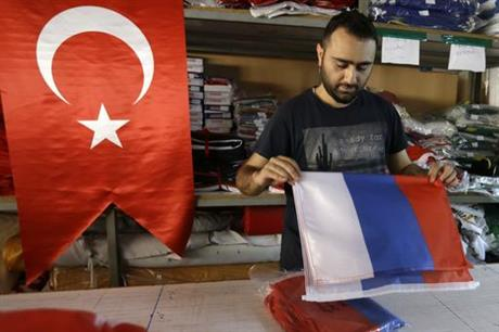 An employee of a flag-making factory folds a Russian flag as a Turkish flag adorns the display at left, in Istanbul, Tuesday, Aug. 9, 2016. AP