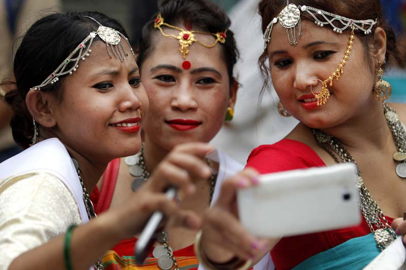 Women in traditional attires take a selfie as they participate in a rally to mark the International Day of World's Indigenous People, in Kathmandu, on Tuesday, August 9, 2016. Photo: AP