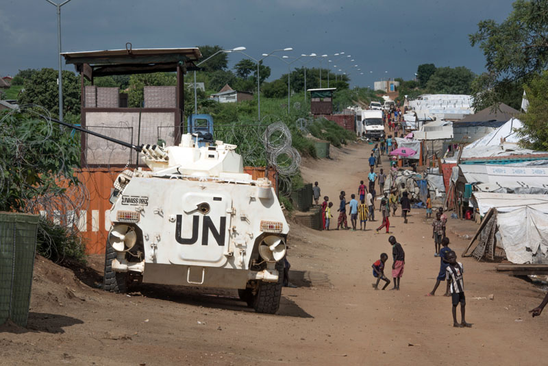 FILE - Some of the more than 30,000 civilians sheltering in a United Nations base in South Sudan's capital Juba for fear of targeted killings by government forces walk by an armored vehicle and a watchtower manned by Chinese UN peacekeepers, on Monday, July 25, 2016. According to reports from victims which have come to light Monday August 15, 2016, South Sudanese troops, fresh from winning a battle against opposition forces in the capital, Juba, on July 11, 2016,  went on a nearly four-hour rampage through a residential compound popular with foreigners, and the UN peacekeeping force stationed nearby are accused of refusing to respond to desperate calls for help. Photo: AP