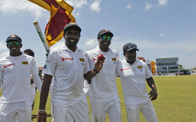 Sri Lankan cricketers from left, Vishwa Fernando, Dilruwan Perera, Angelo Mathews and Rangana Herath acknowledge the crowd as they celebrate their victory over Australia by 229 runs in the second test cricket match in Galle, Sri Lanka, Saturday, Aug. 6, 2016. (AP Photo/Eranga Jayawardena)