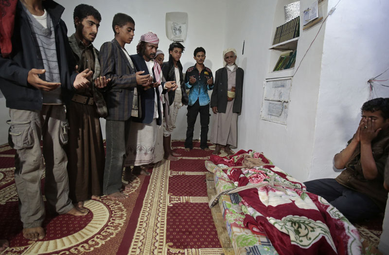 Mourners pray over the body of 10-year-old Youssef al-Salmi, who was killed when a bomb exploded while he was playing with it near his family's house, in Hasn Faj Attan village, on the mountainous outskirts of Sanaa, Yemen, on July, 24, 2016. Photo: AP