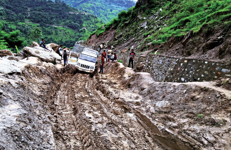 Locals looking at a vehicle stuck on a muddy road at Falasain along the Sanfe-Martadi road section, in Bajura, on Friday.