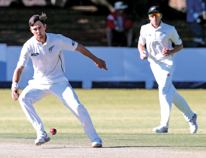New Zealand bowler Trent Boult fields off his own bowling during the fourth day of the second test in a series of two matches between New Zealand and host Zimbabwe on August 9 2016 at the Queens Sports Club in Bulawayo. Photo: AFP