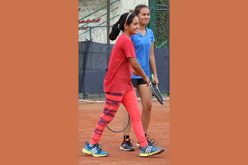 Abhilasha Bista and Ira Rawat (right) celebrate after winning the womenu2019s doubles title of the first National Open Lawn Tennis Tournament in Lalitpur on Sunday, September 25, 2016. Photo: THT