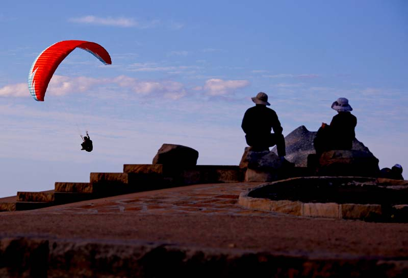 People watch as a paraglider flies past them as they sit atop Long Reef Point on the first day of Spring in Sydney, Australia, on September 1, 2016. Photo: Reuters