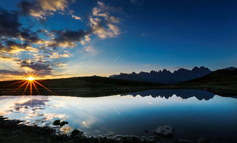 The sun rises as mountains are reflected in a small lake in the western Austrian village of Grinzens, Austria, on September 2, 2016. Photo: Reuters