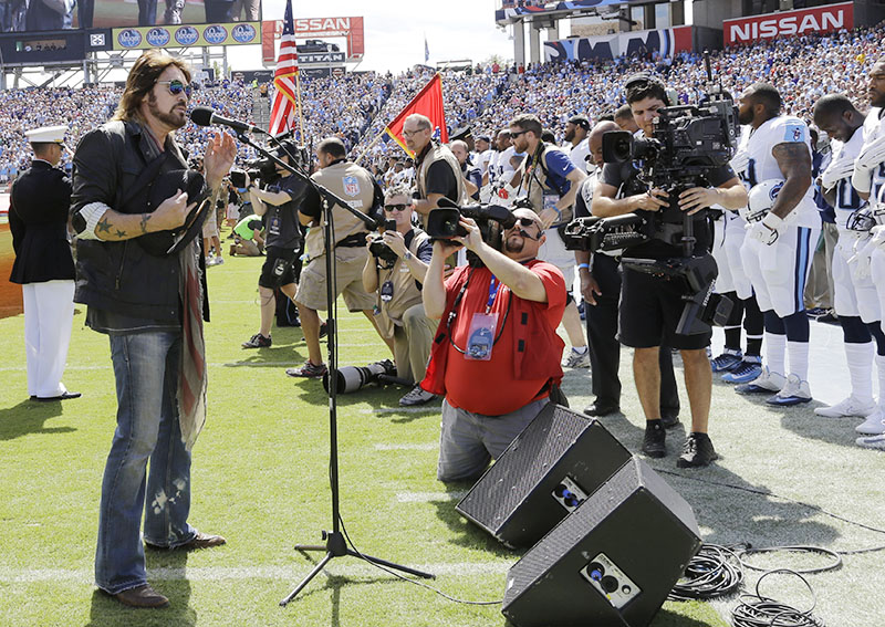 FILE - Tennessee Titans players, including Wesley Woodyard (far right), Jason McCourty, (second from right) and Jurrell Casey, (third from right) stand during the singing of the national anthem by Billy Ray Cyrus (left), before an NFL football game against the Minnesota Vikings in Nashville, Tennessee, on September 11, 2016. Photo: AP
