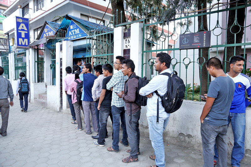 Rastriya Banijya Bank customers queue to withdraw money from its ATM booth in New Baneshwor, Kathmandu, on Sunday, September 18, 2016. Photo: RSS