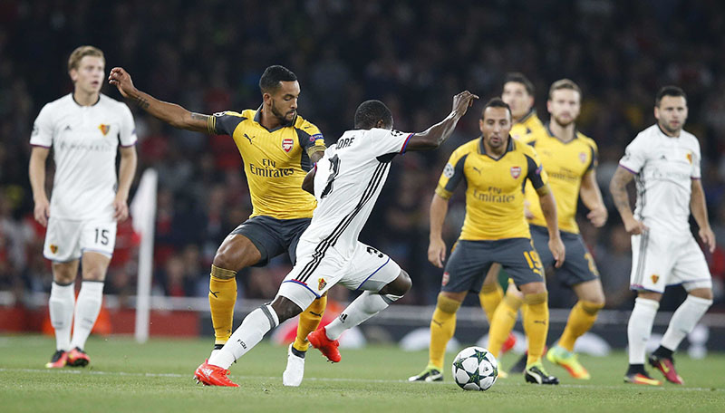 Arsenal's Theo Walcott challenges Basel's Adama Traore during the Champions League group A soccer match between Arsenal and Basel at the Emirates stadium in London, on Wednesday, September 28, 2016. Photo: AP