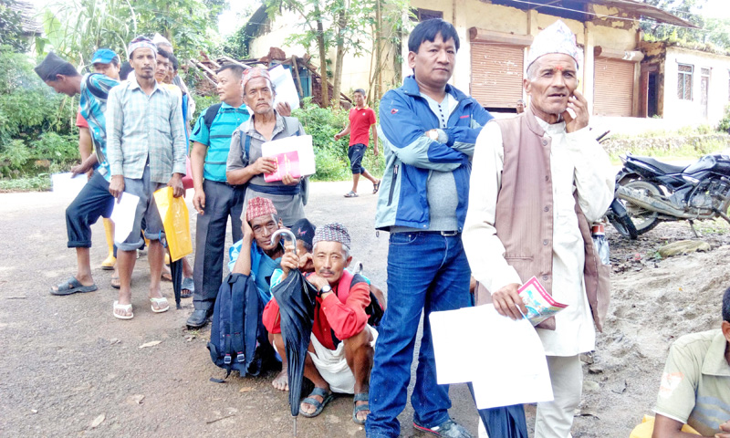 Earthquake victims queue infront of Rastriya Banajiya Bank, to receive the first installment of housing grant, in Kharanitar of Nuwakot district, on Tuesday, September 13, 2016. Photo: RSS