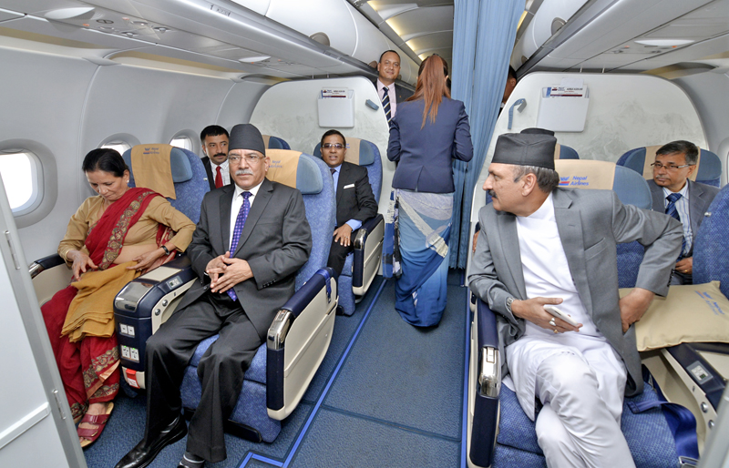 Prime Minister Pushpa Kamal Dahal and Minister for Foreign Affairs Prakash Sharan Mahat chit-chat on board a Nepal Airlines flight as the PM embarks on a four-day state visit to India, on Thursday, September 15, 2016. Photo: RSS