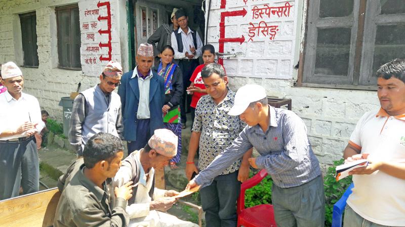 Bajura district Deputy Secretary Gagan Rawal of CPN-UML handing over Rs 30,000 offered by Dr Sundar Mani Dixit, to Dip Chandara, 64, a Dalit, at Kolti VDC, Bajura, on Thursday, September 8, 2016. Photo: THT