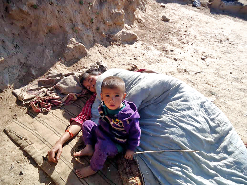A woman suffering from viral fever lying in her house yard, in Gudukhati VDC, Bajura, on Wednesday, September 21, 2016. Photo: THT