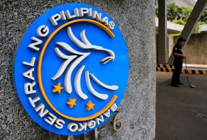 A security guard stands beside a logo of the Bangko Sentral ng Pilipinas (Central Bank of the Philippines) posted at the main gate in Manila, Philippines April 28, 2016.    REUTERS/Romeo Ranoco/File Photo
