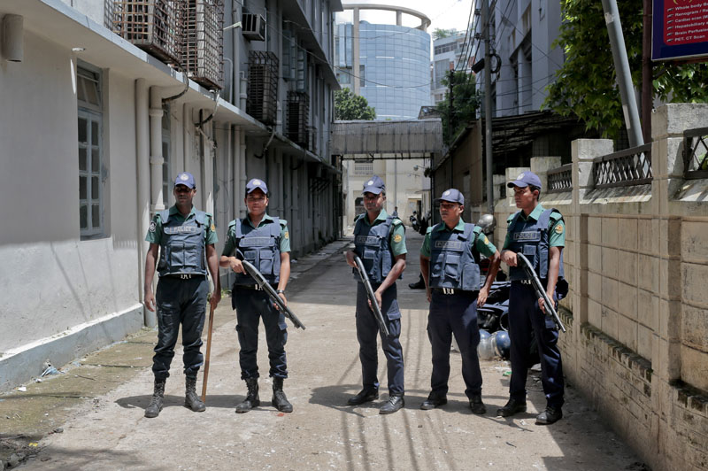 Bangladeshi policemen stand guard outside a morgue at the Dhaka Medical College Hospital during the autopsy on the bodies of suspected Islamic militants who were killed in Dhaka, Bangladesh, on  on Wednesday, July 27, 2016. Photo: AP