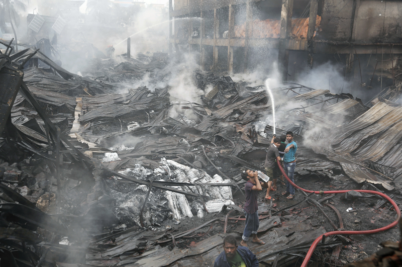 Bangladeshi people and firefighters work to put out a fire at a packaging factory in the Tongi industrial area, outside Dhaka, Bangladesh, Sunday, September 11, 2016. Photo: AP