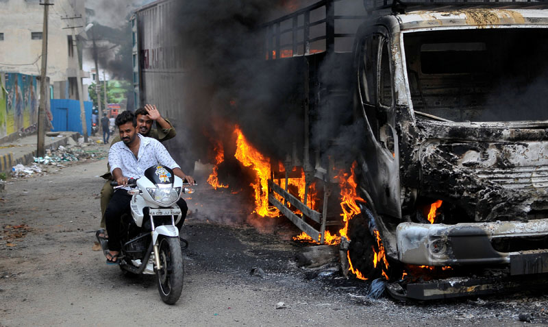 Men ride a motorcycle past a lorry in Bengaluru, which was set on fire by protesters after India's Supreme Court ordered Karnataka state to release 12,000 cubic feet of water per second every day from the Cauvery river to neighbouring Tamil Nadu, India, on September 12, 2016. Photo: Reuters